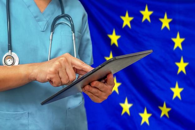 Chirurg oder arzt, der ein digitales tablett auf dem hintergrund der flagge der europäischen union verwendet