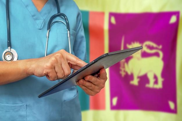 Chirurg oder arzt, der ein digitales tablett auf dem hintergrund der flagge von sri lanka verwendet