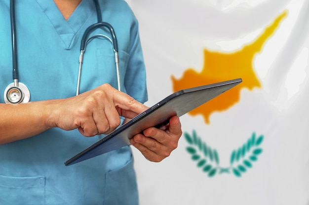 Chirurg oder arzt, der ein digitales tablett auf dem hintergrund der flagge zyperns verwendet