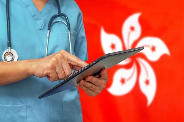 Chirurg oder arzt, der ein digitales tablett auf dem hintergrund der hongkong-flagge verwendet