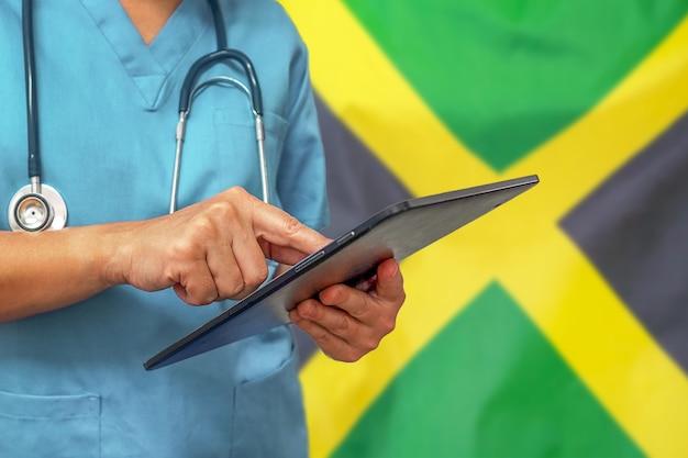 Chirurg oder arzt, der ein digitales tablett auf dem hintergrund der jamaika-flagge verwendet