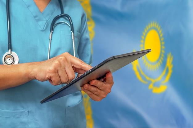 Chirurg oder arzt, der ein digitales tablett auf dem hintergrund der kasachischen flagge verwendet