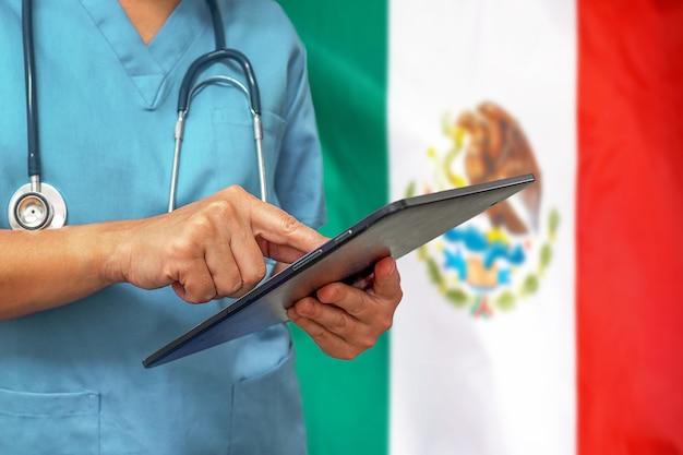 Chirurg oder arzt, der ein digitales tablett auf dem hintergrund der mexiko-flagge verwendet