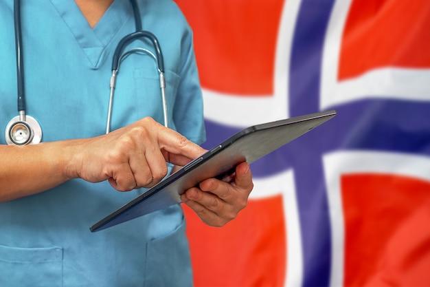 Chirurg oder arzt, der ein digitales tablett auf dem hintergrund der norwegischen flagge verwendet