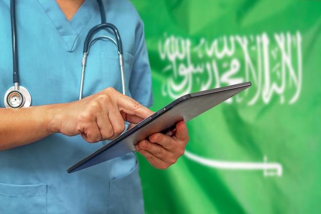 Chirurg oder arzt, der ein digitales tablett auf dem hintergrund der saudi-arabien-flagge verwendet