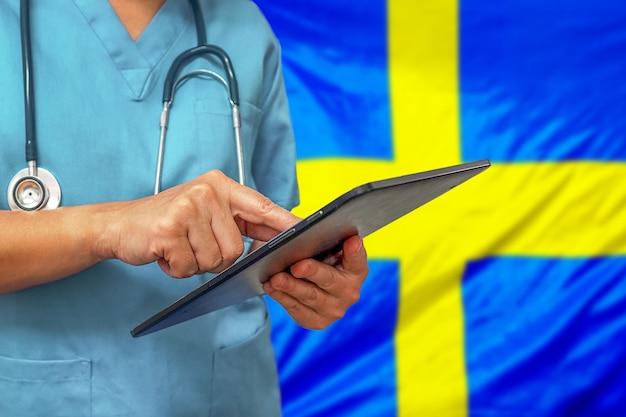 Chirurg oder arzt, der ein digitales tablett auf dem hintergrund der schwedenflagge verwendet