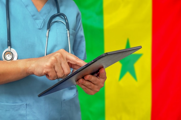 Chirurg oder arzt, der ein digitales tablett auf dem hintergrund der senegalesischen flagge verwendet