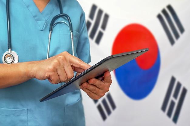 Chirurg oder arzt, der ein digitales tablett auf dem hintergrund der südkorea-flagge verwendet