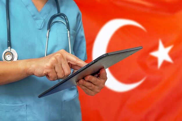 Chirurg oder arzt, der ein digitales tablett auf dem hintergrund der türkischen flagge verwendet
