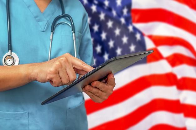 Chirurg oder arzt, der ein digitales tablett auf dem hintergrund der usa-flagge verwendet