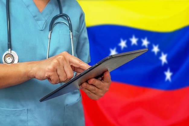 Chirurg oder arzt, der ein digitales tablett auf dem hintergrund der venezuela-flagge verwendet