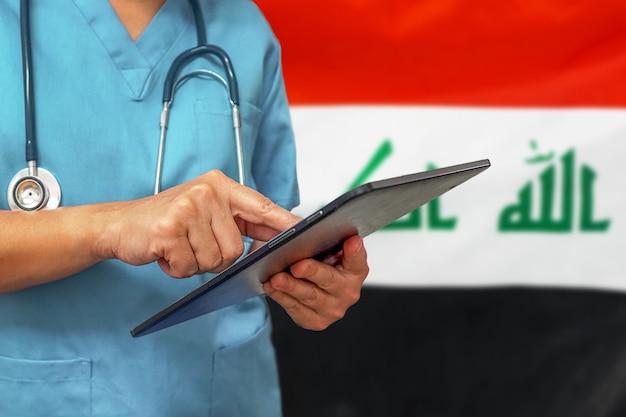 Chirurg oder arzt mit einem digitalen tablet auf dem hintergrund der irak-flagge