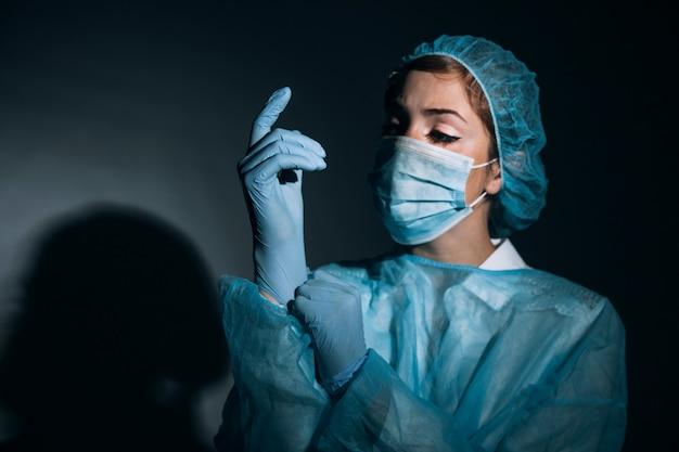 Chirurg trägt handschuhe in der dunkelheit