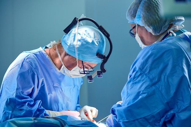 Chirurg und sein assistent, die kosmetische chirurgie im krankenhausoperationsraum durchführen.