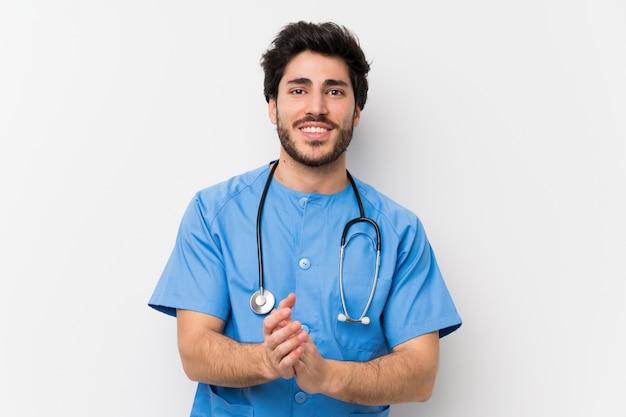 Chirurgdoktormann über lokalisiertem weißem wandapplaudieren
