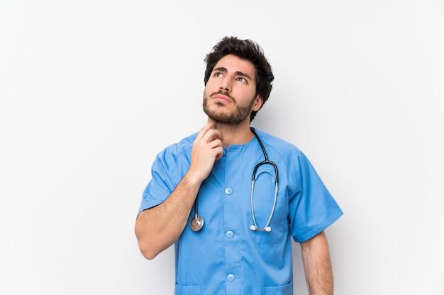 Chirurgdoktormann über lokalisierter weißer wand, die eine idee steht und denkt