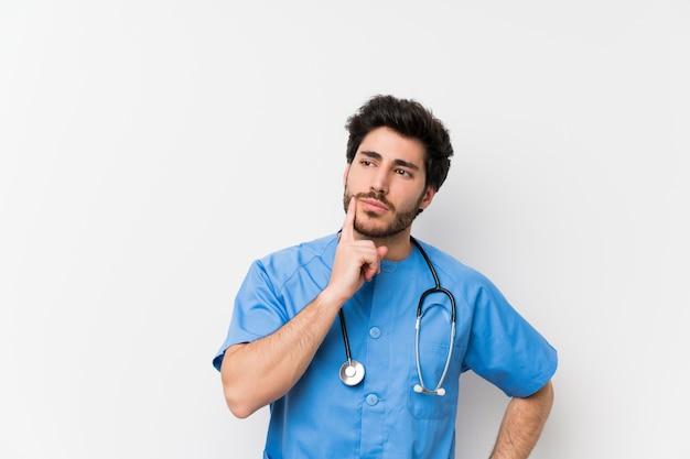 Chirurgdoktormann über lokalisierter weißer wand eine idee denkend