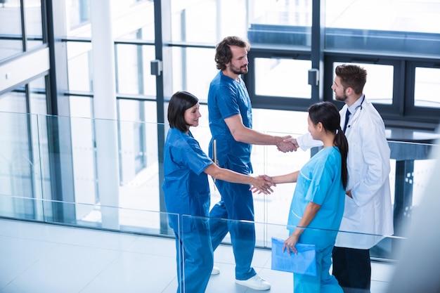 Chirurgen, arzt und krankenschwester geben sich die hand