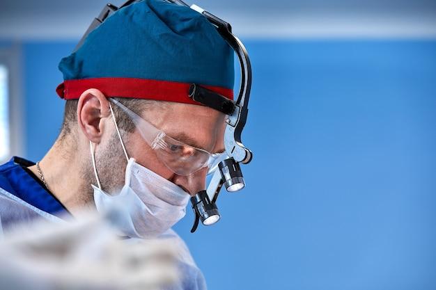 Chirurgie. das gesicht eines chirurgen in einer maske auf dem hintergrund des operationssaals, nahaufnahme eines arbeitenden arztes. kopieren sie platz, operationen, moderne medizin, plastische chirurgie