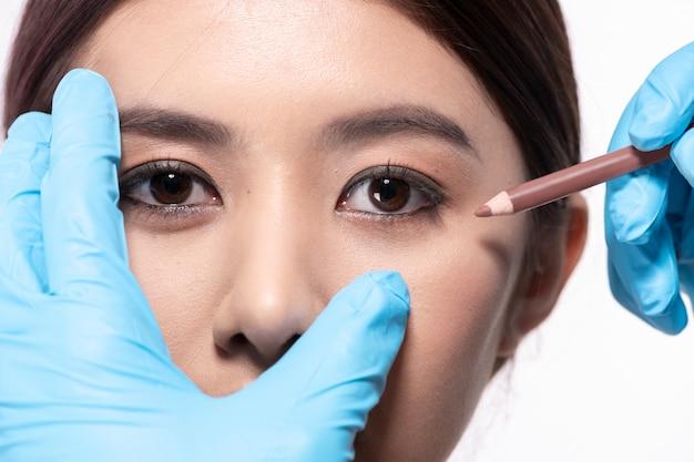 Chirurgie-konzept der arzt zeichnet einen bleistift auf das gesicht des patienten. der patient ist zuversichtlich in die operation des arztes.