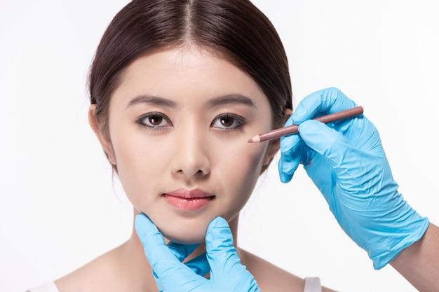 Chirurgie-konzept der arzt zeichnet einen bleistift auf das gesicht des patienten