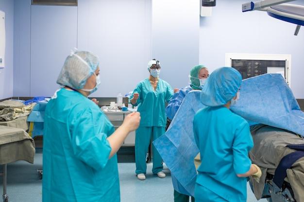 Chirurgie, medizin und personenkonzept - gruppe von chirurgen im operationssaal des krankenhauses, die sprechen und sich auf die operation vorbereiten