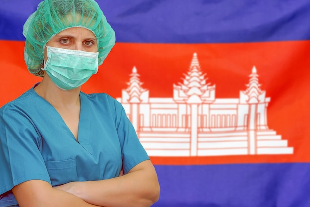 Chirurgin in maske und hut betrachtet die kamera auf dem hintergrund der kambodscha-flagge