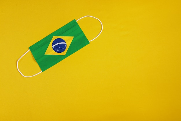 Chirurgische maske auf gelbem hintergrund mit brasilianischer flagge