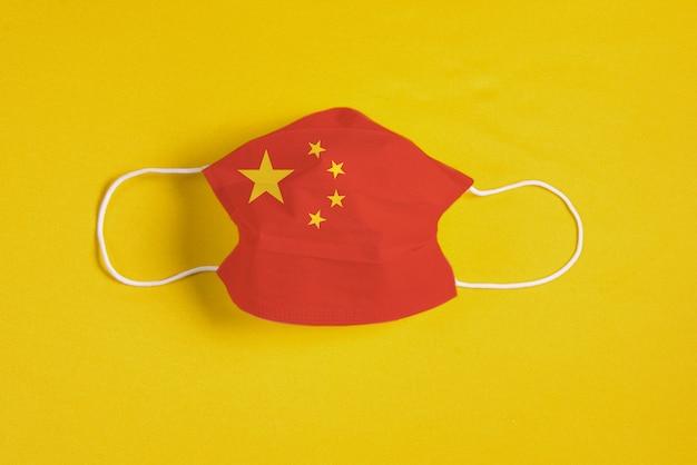 Chirurgische maske auf gelbem hintergrund mit flagge von china