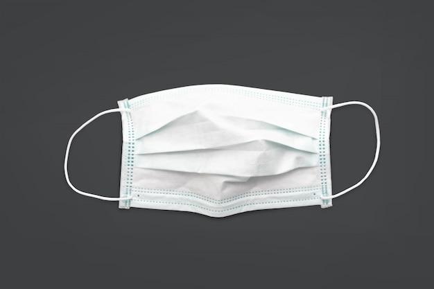 Chirurgische maske mit gummi-ohrriemen auf schwarzem hintergrund