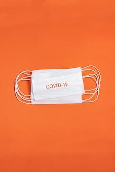Chirurgische maske über minimalistischem orangefarbenem hintergrund