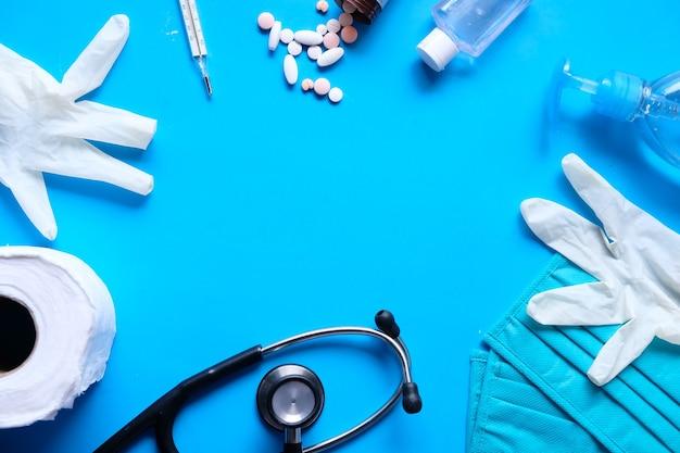 Chirurgische masken, thermometer und händedesinfektionsmittel auf blauem hintergrund