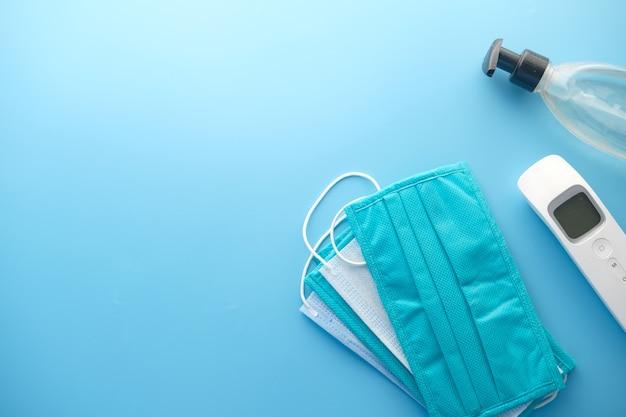 Chirurgische masken, thermometer und händedesinfektionsmittel auf orangefarbenem hintergrund.