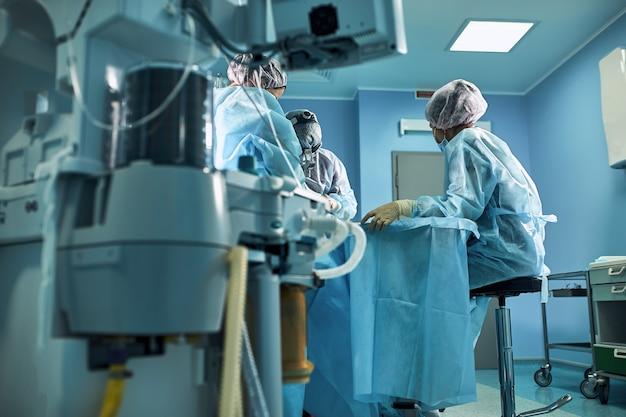 Chirurgischer operationssaal im krankenhaus lebensrettende beatmung der lunge mit sauerstoff vor dem hintergrund eines teams von chirurgen während der operation