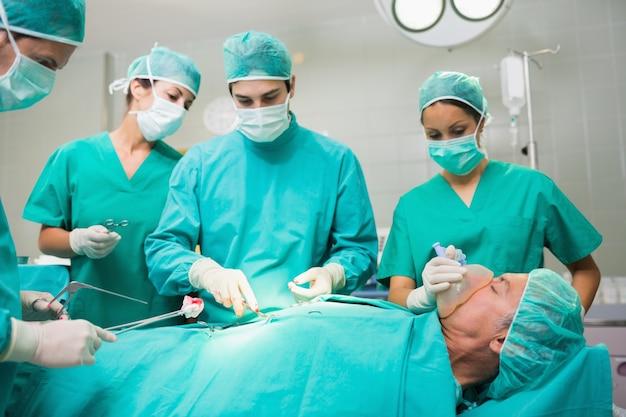 Chirurgisches team, das an einem geduldigen bauch durchführt