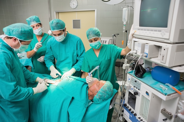 Chirurgisches team, das einen geduldigen bauch betreibt