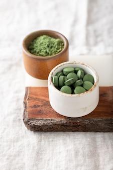 Chlorella-tabletten und spirulina-pulver, konzept von superfood und entgiftung