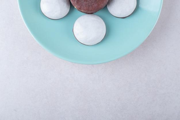 Cholatbeschichtete cookie mini mousse gebäck dessert auf einem teller auf marmortisch.