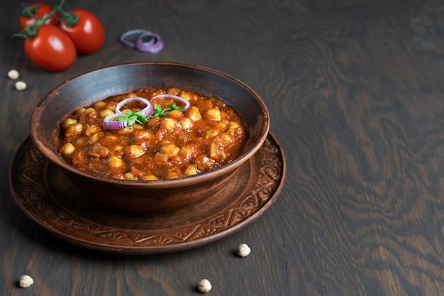 Chole masala indische kichererbsen vegetarisches essen mit tomaten und zwiebeln auf dunklem holztisch