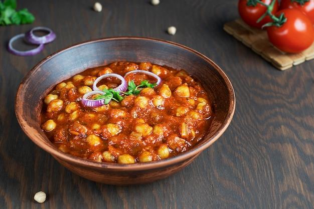 Chole masala indisches veganes essen aus kichererbsen und tomaten serviert in schüssel in der küche auf dem tisch