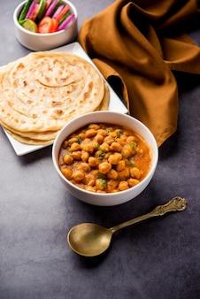 Chole oder chana masala mit paratha, würziges curry aus kichererbsen, serviert mit laccha parantha. beliebtes nordindisches gericht