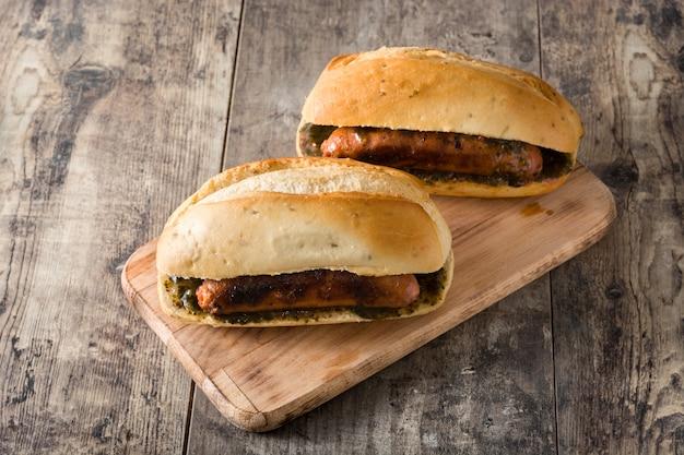 Choripan traditionelles argentinien-sandwich mit chorizo und chimichurri sauce auf holztisch