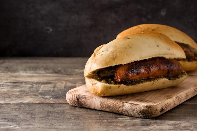 Choripan. traditionelles argentinien-sandwich mit chorizo und chimichurri sauce auf holztisch