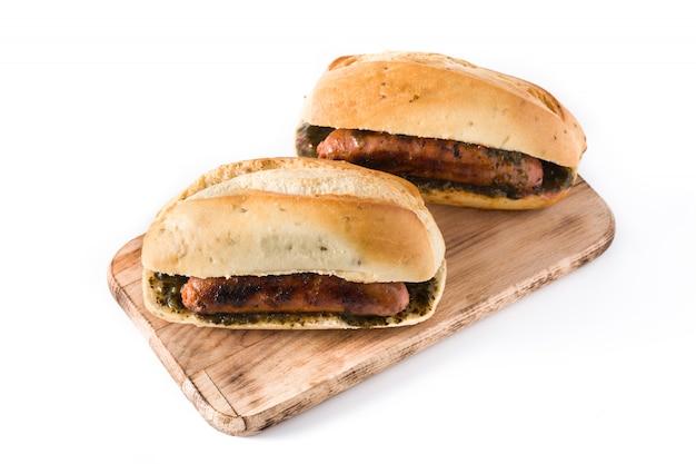 Choripan traditionelles argentinien-sandwich mit chorizo und chimichurri-sauce. isoliert auf weiß