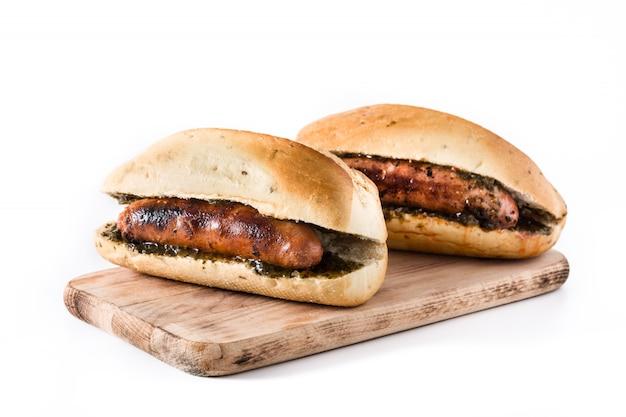 Choripan. traditionelles argentinien-sandwich mit chorizo und chimichurri-sauce. isoliert auf weiß
