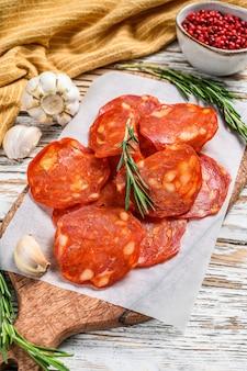 Chorizo-wurst dünn geschnitten auf einem schneidebrett. spanische salami mit gewürzen, paprika, pfeffer. scharfes essen. weißer hintergrund. draufsicht.