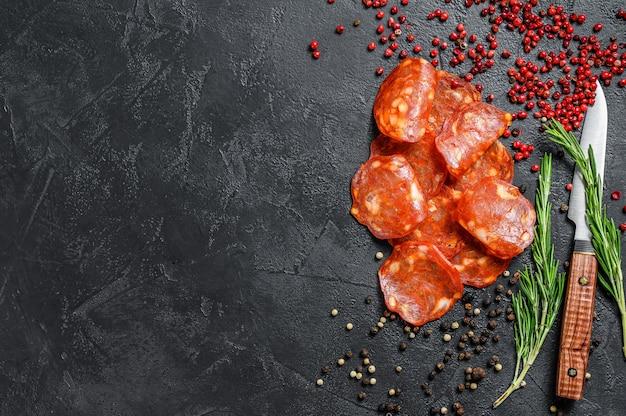 Chorizo wurst dünn geschnitten. spanische salami mit gewürzen, paprika, pfeffer. scharfes essen. schwarzer hintergrund. draufsicht. speicherplatz kopieren.