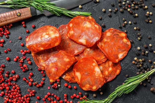 Chorizo wurst dünn geschnitten. spanische salami mit gewürzen, paprika, pfeffer. scharfes essen. schwarzer hintergrund. draufsicht.