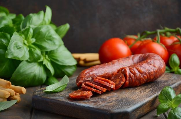 Chorizo-wurst. spanische traditionelle chorizo-wurst mit frischen kräutern und tomaten.