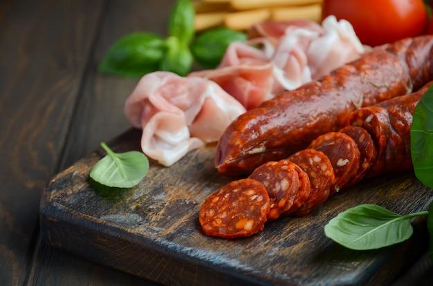 Chorizo-wurst. spanische traditionelle chorizowurst und schinken mit frischen kräutern und tomaten.